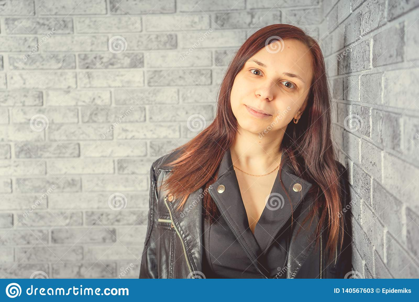 Portrait of a young girl without makeup on her face in a black jacket against a gray brick wall.