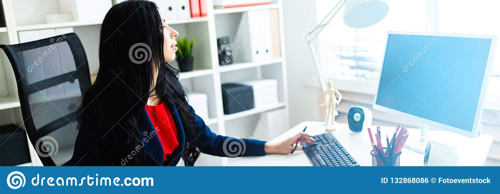 Beautiful young girl working with computer and documents in the office at the table.
