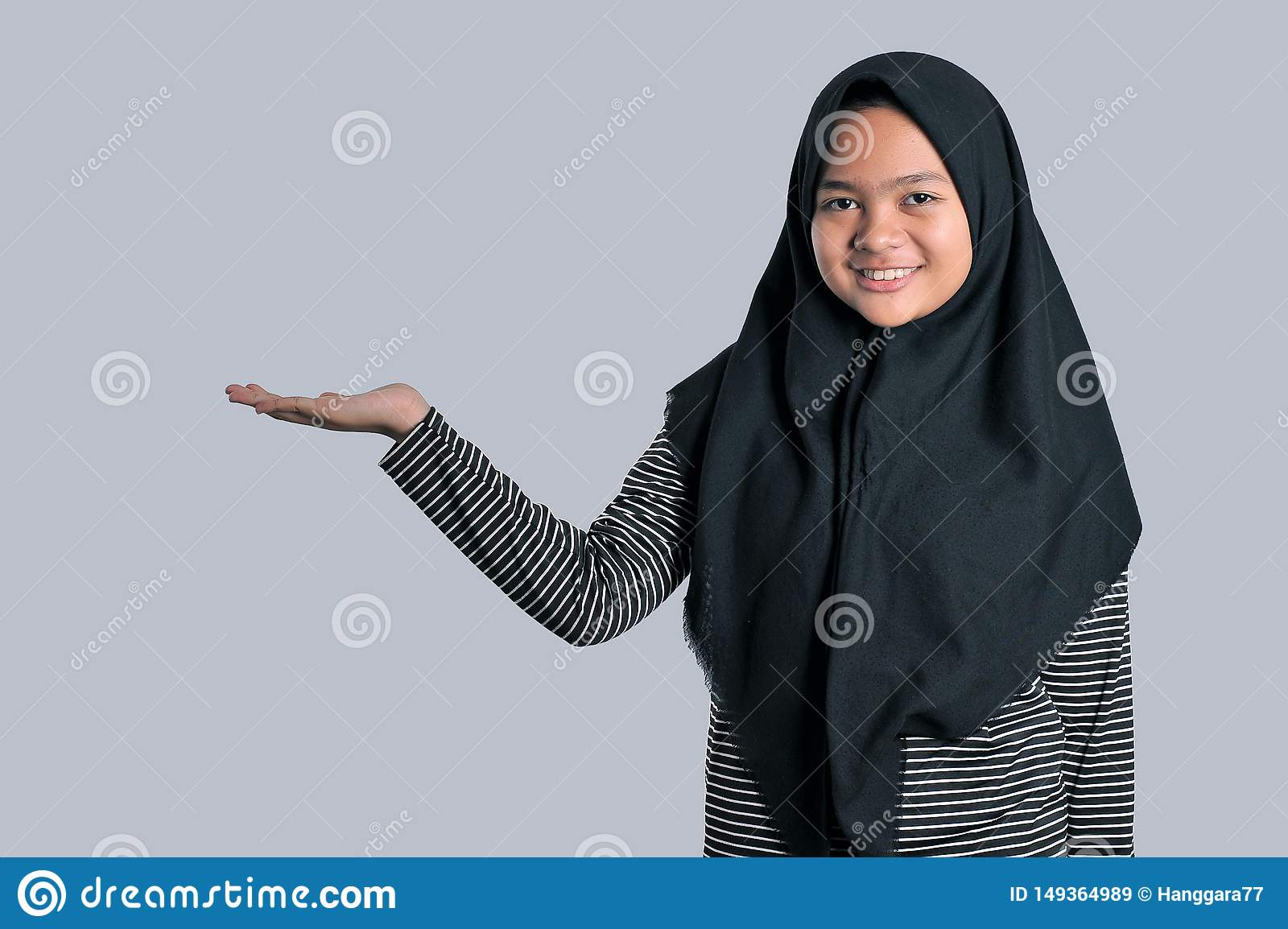 Portrait of a young girl wearing islamic headscarf showing blank area for sign or copyspase