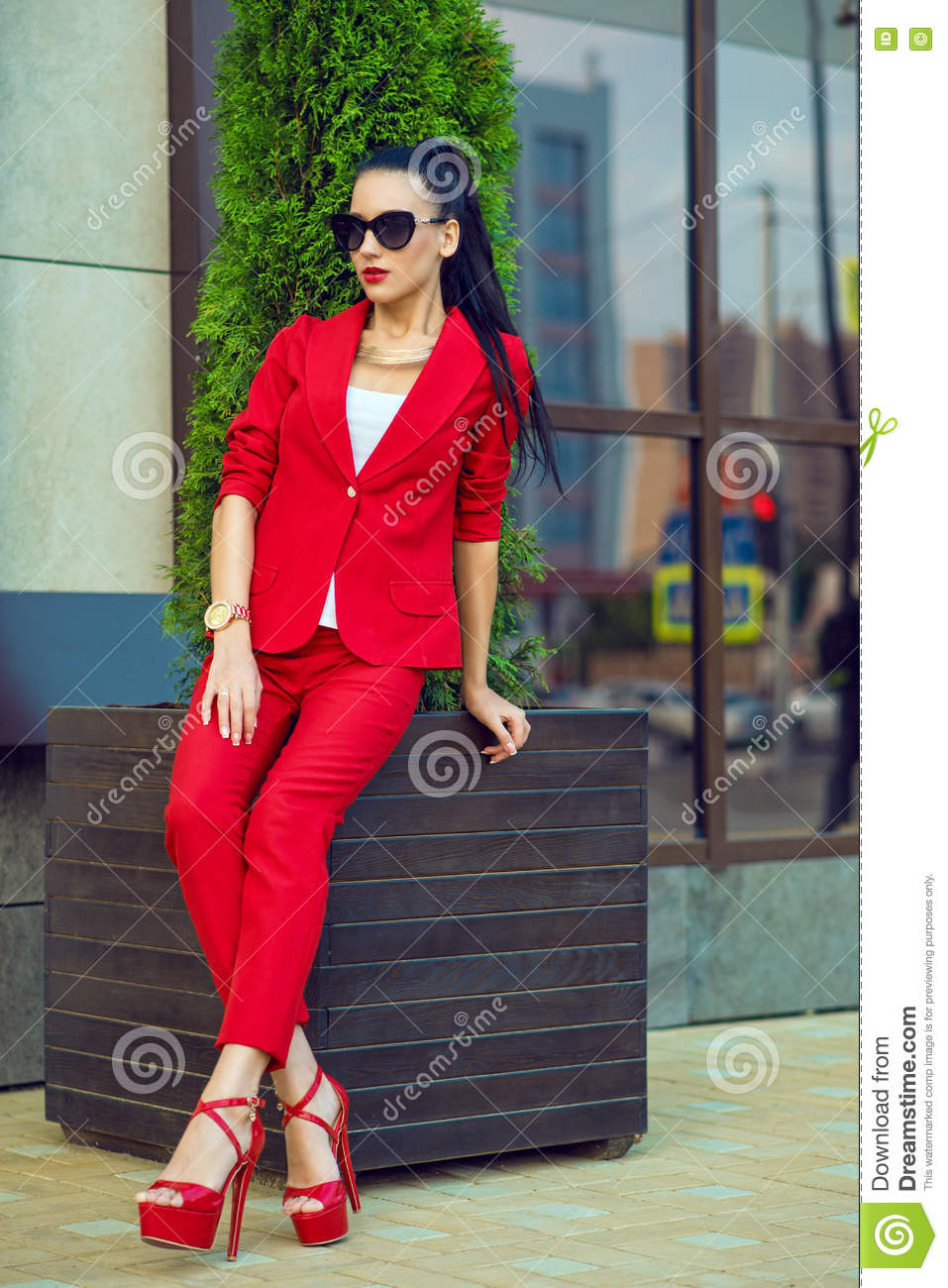 Portrait of young gorgeous dark-haired businesswoman in sunglasses and bright red suit sitting at the office building