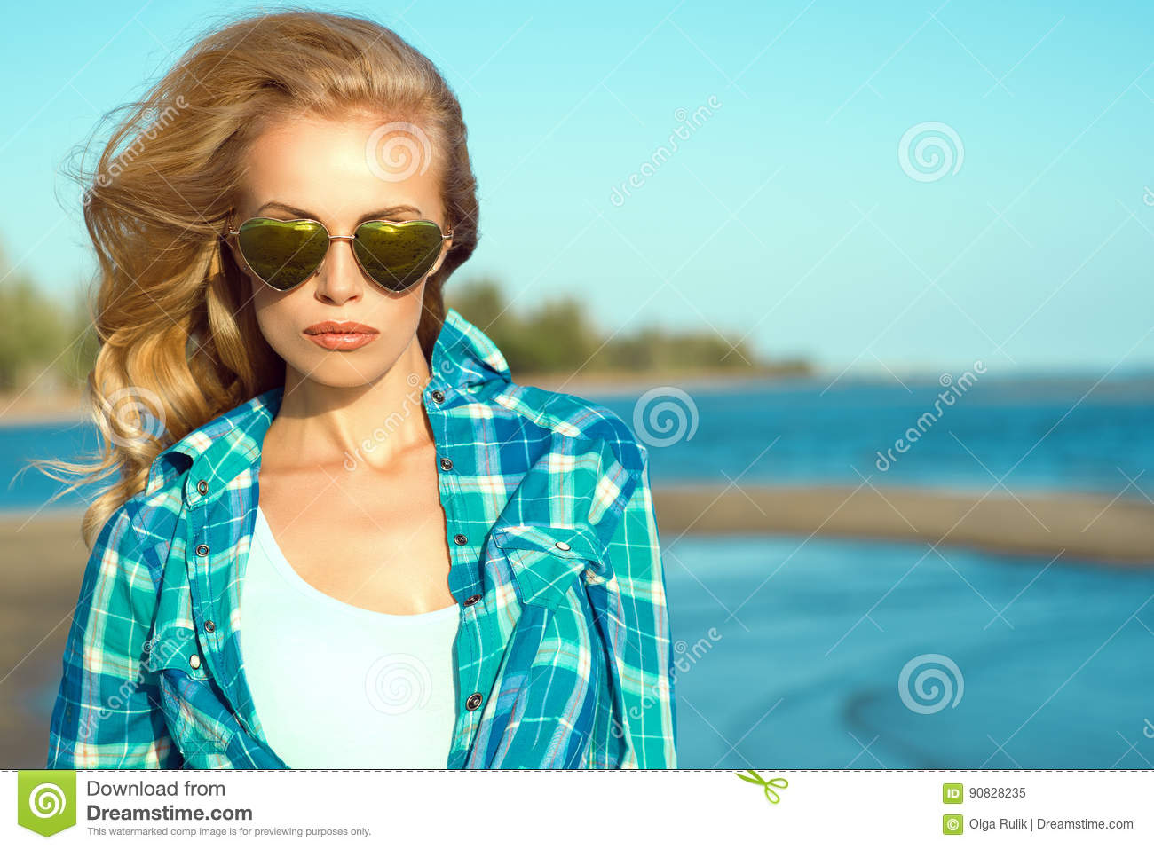 Portrait of young gorgeous suntanned blond model wearing mirrored heart shaped sunglasses and checked blue shirt at the sea