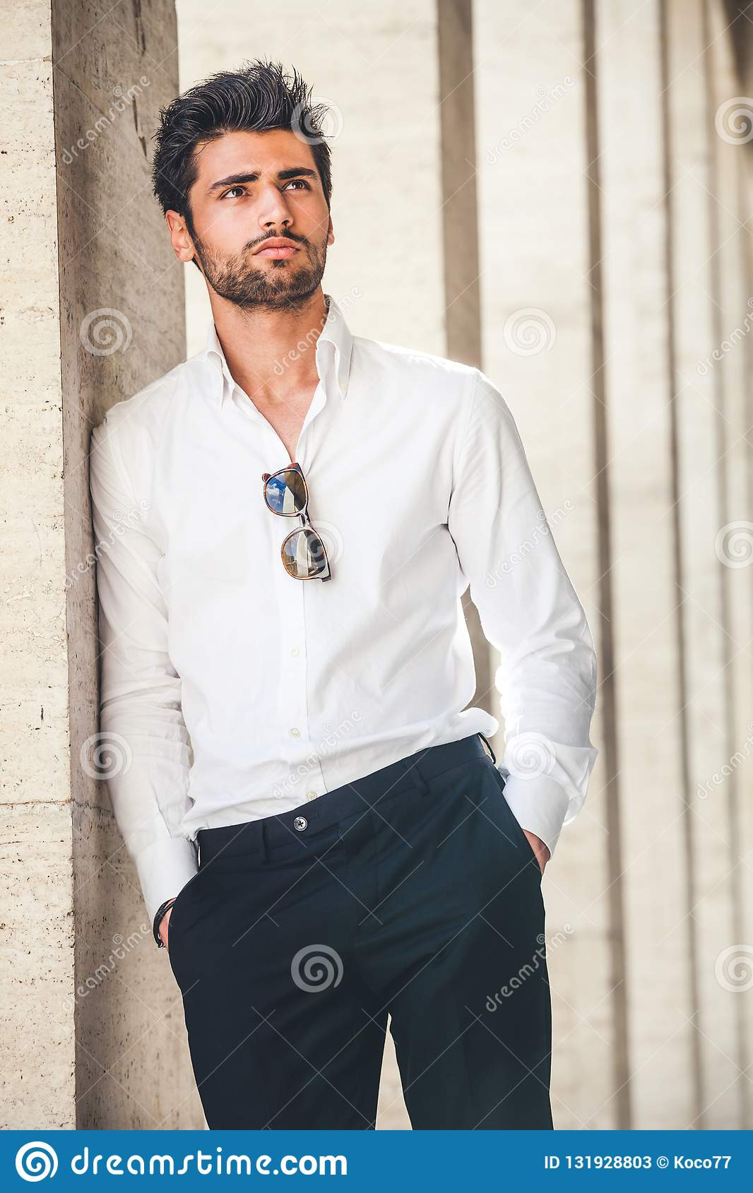 Portrait of young handsome man in white shirt outdoor.