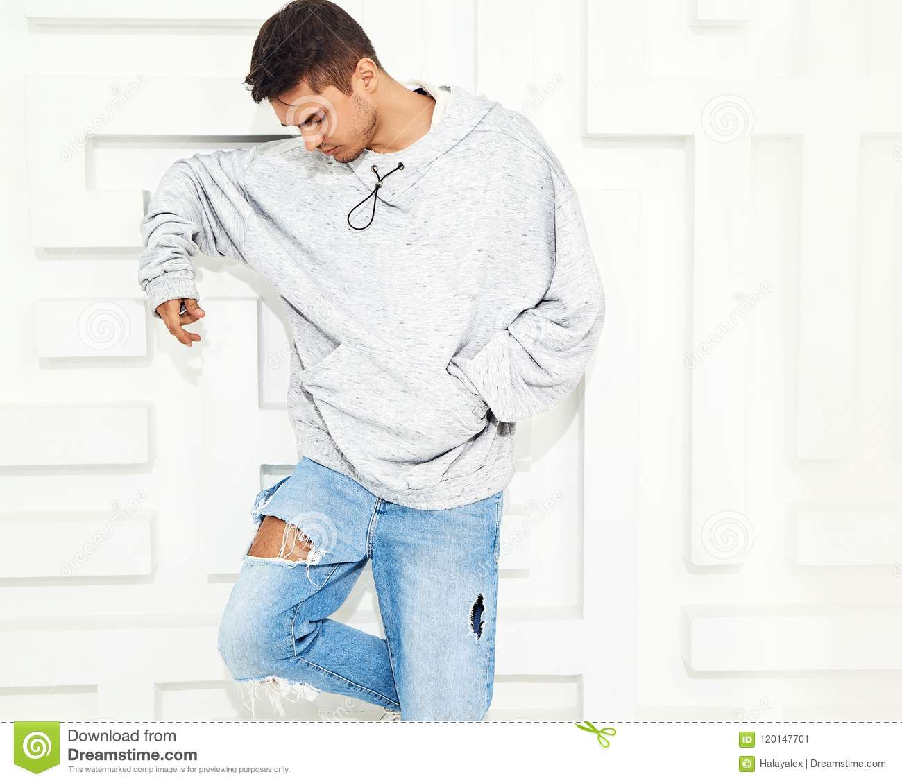 80081af901 Portrait of young handsome model man dressed in gray casual hoodie clothes  posing near textured white wall
