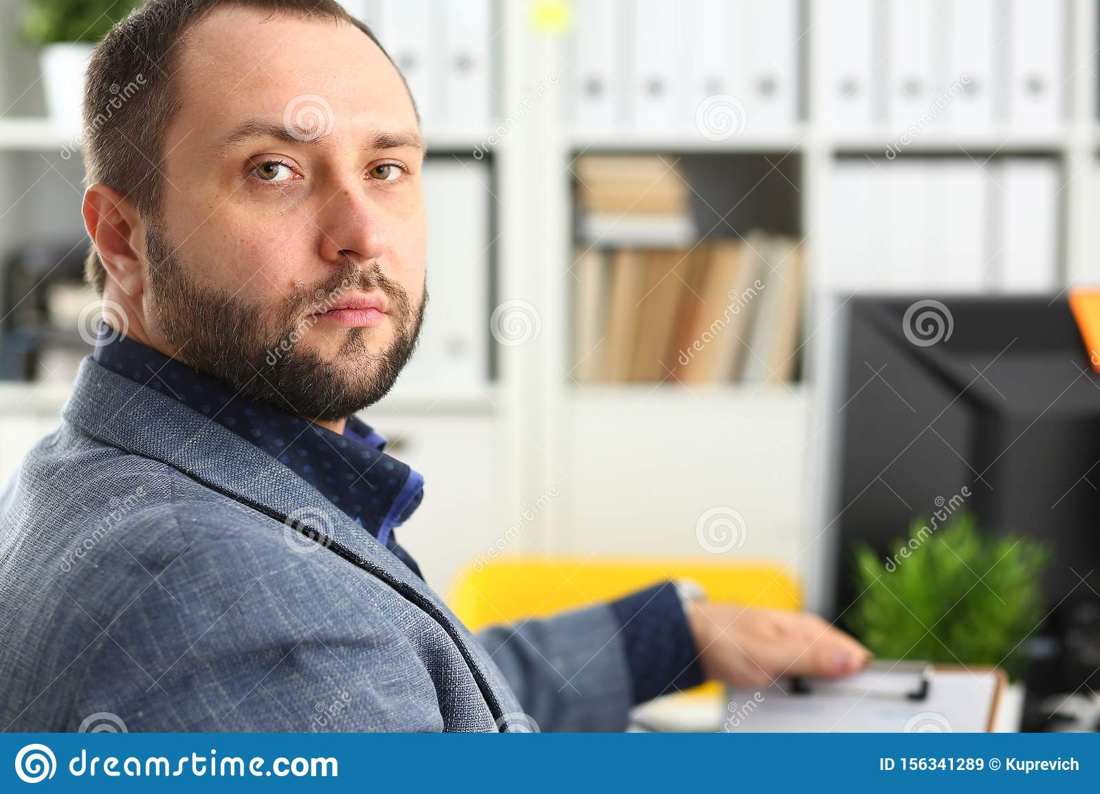 Portrait of young handsome promising businessman in office