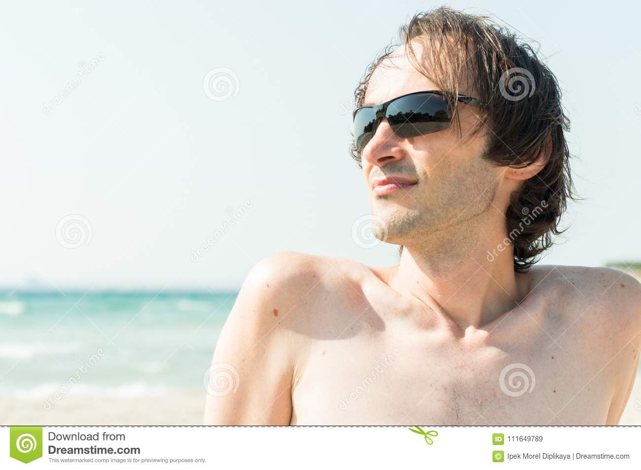 964ded671e44 Portrait of a young happy Caucasian man with sunglasses enjoying the sun  near seaside