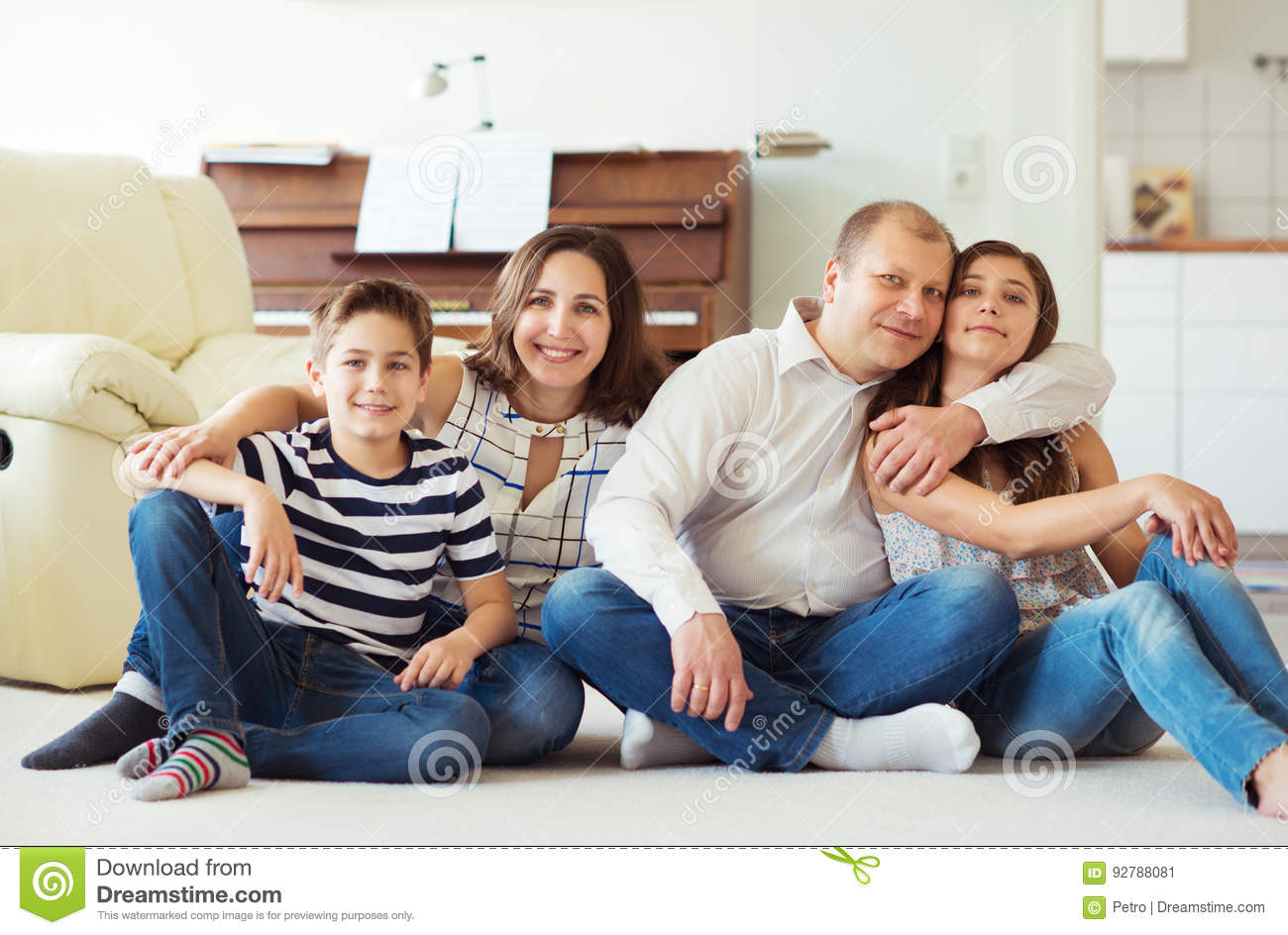 Portrait of young happy family with pretty teenager daughter and