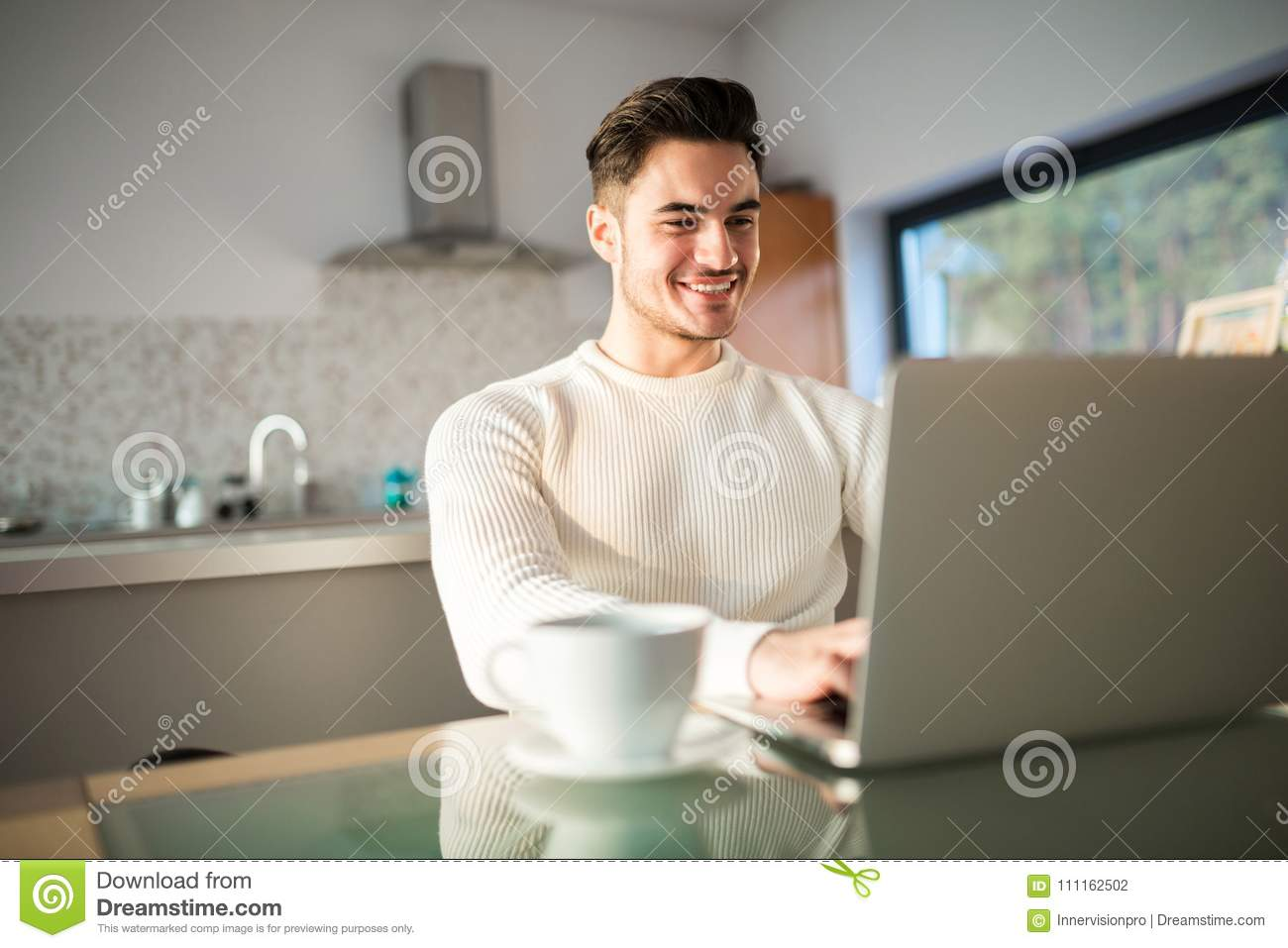 Young happy man working at home on laptop