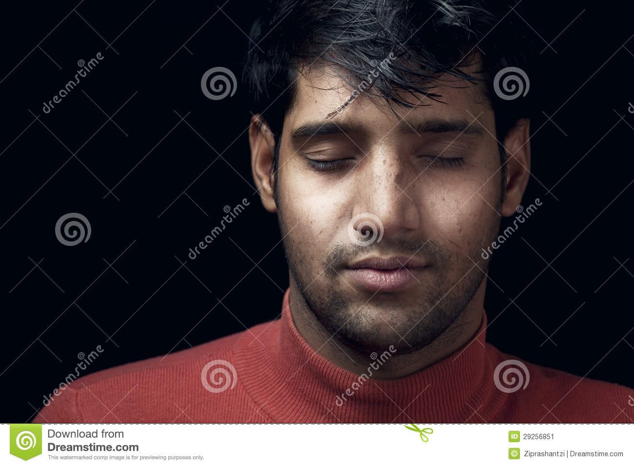 Stock Image: Portrait of young Indian man closed eyes over dark