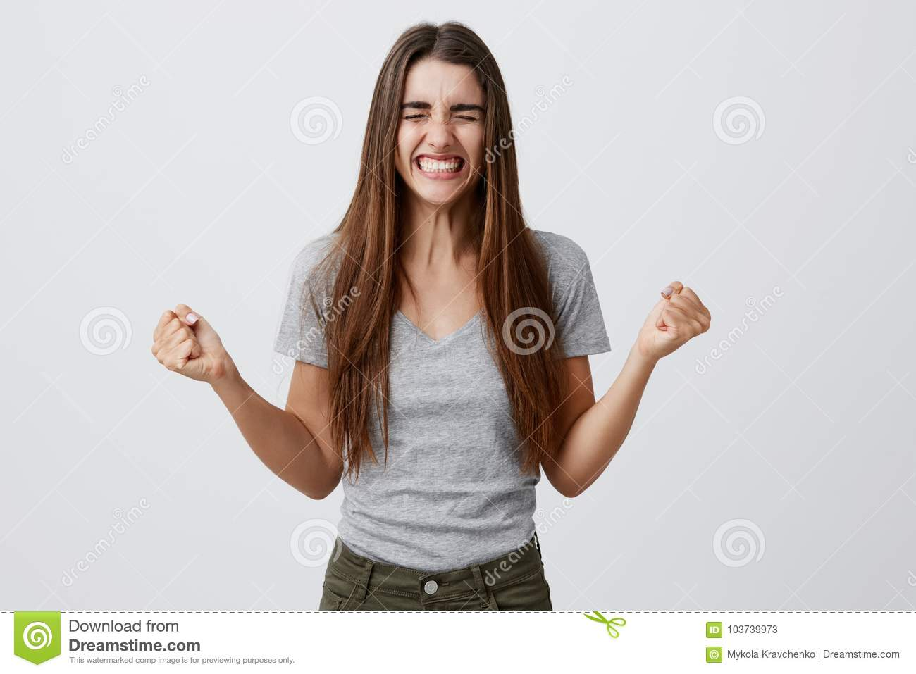 Portrait of young joyful happy beautiful female student with long dark hair in casual gray outfit smiling with teeth