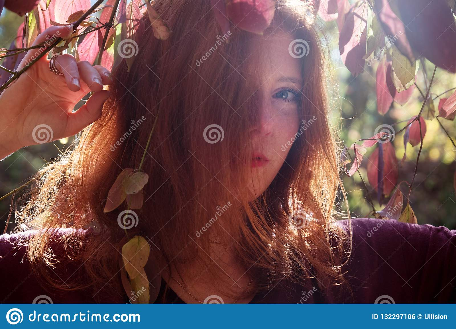 Portrait of a young lovely foxy girl with violet top, beautiful attractive fiery woman, ginger, redhead, under a bush
