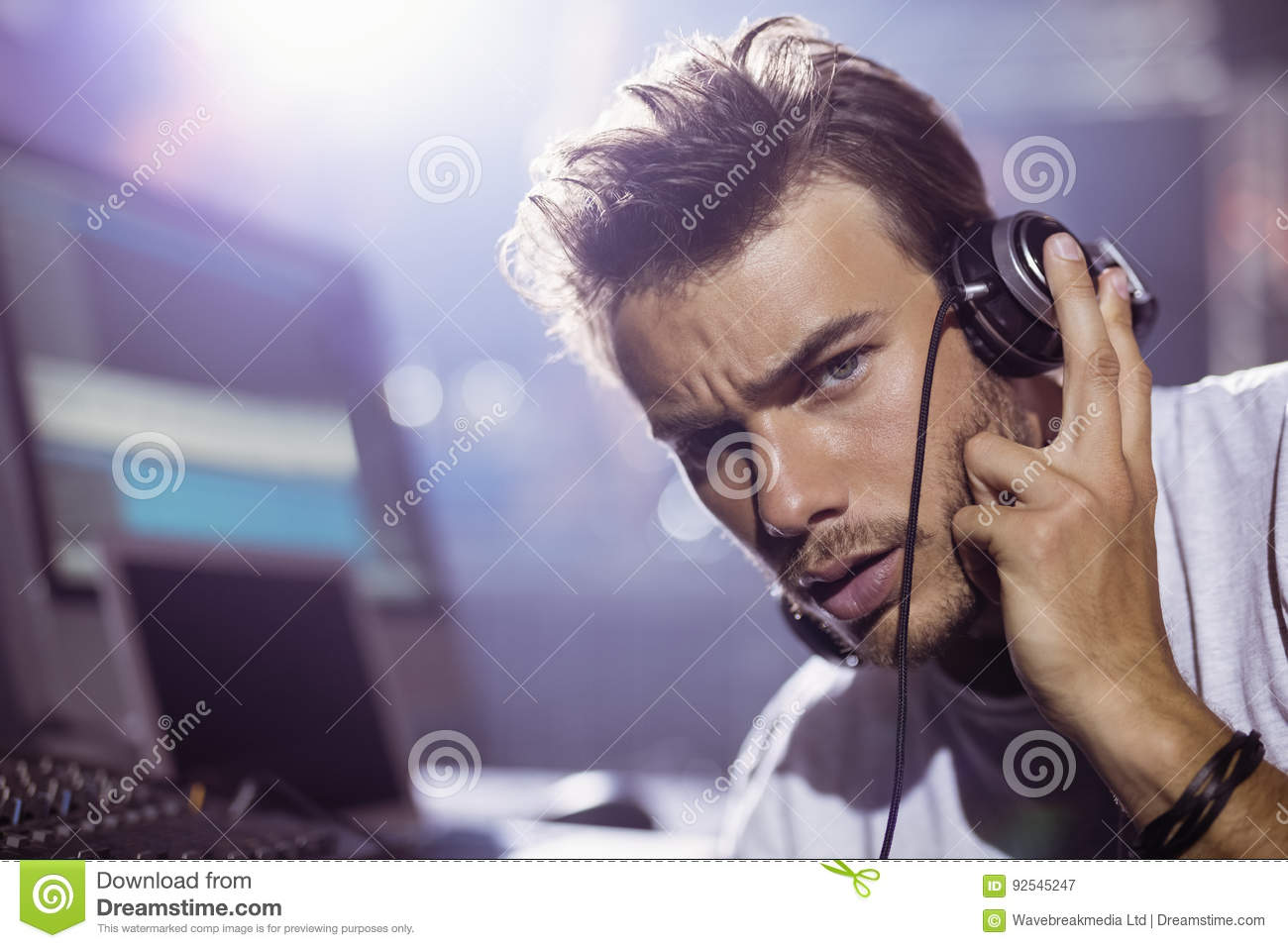Portrait of young male dj with headphones at nightclub