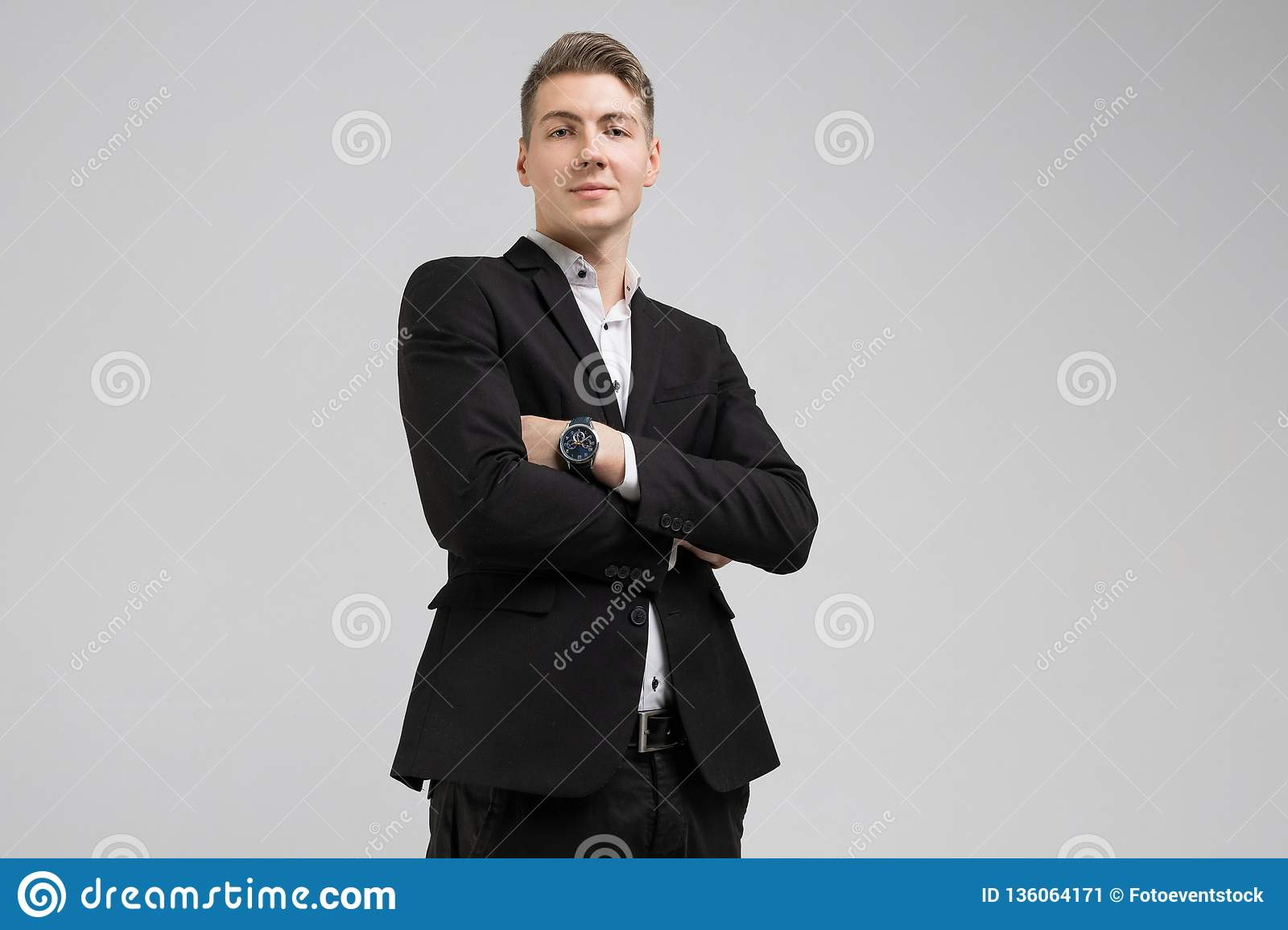 2937012495 Portrait of young man in black suit with arms crossed isolated on white  background