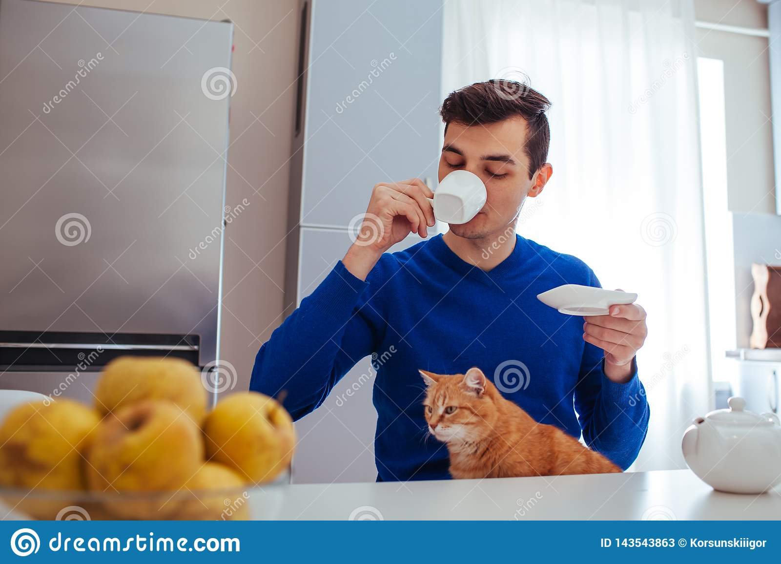 Portrait of a young man drinking tea with a cat on kitchen