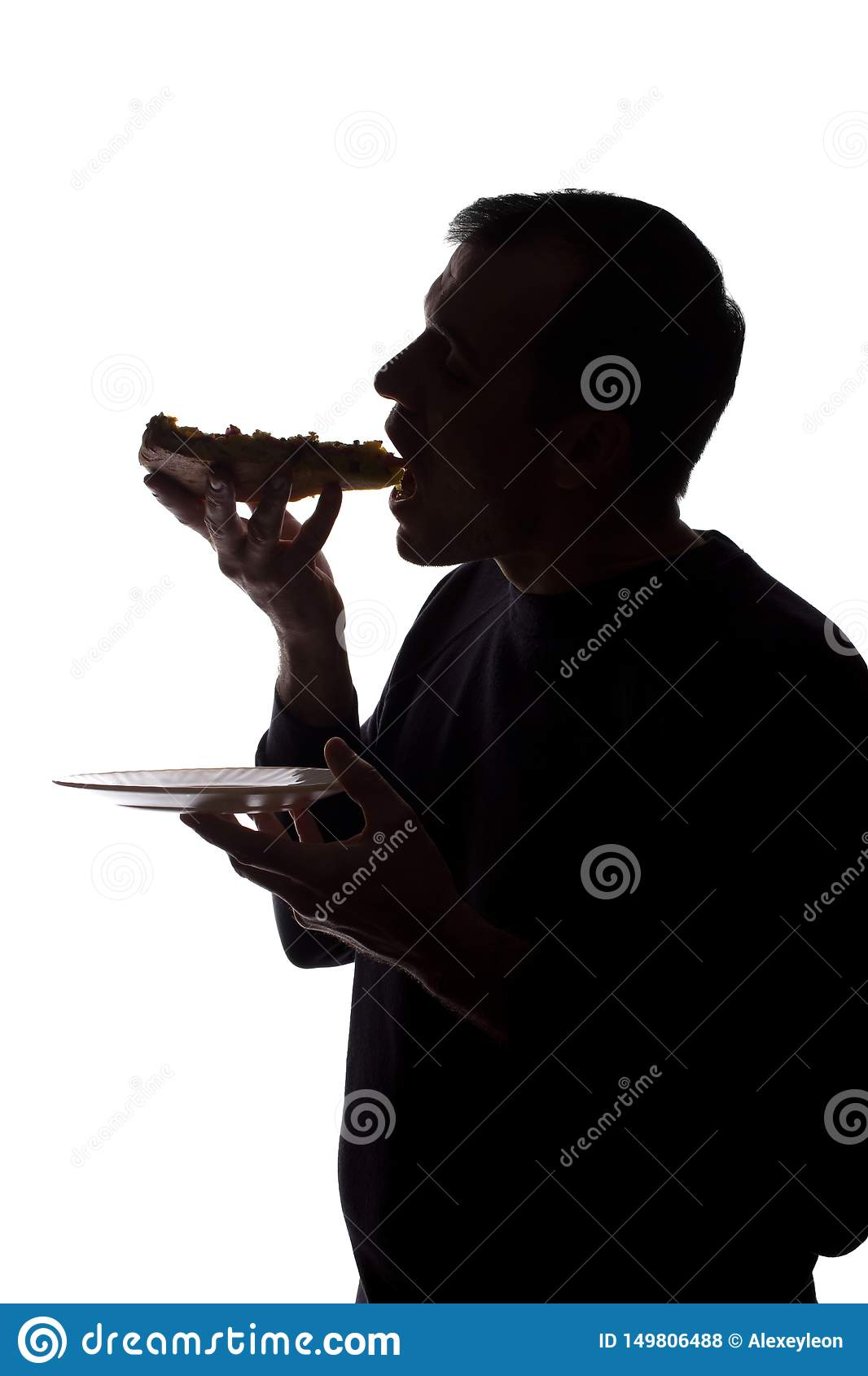 Portrait of a young man eat pizza, side view - silhouette