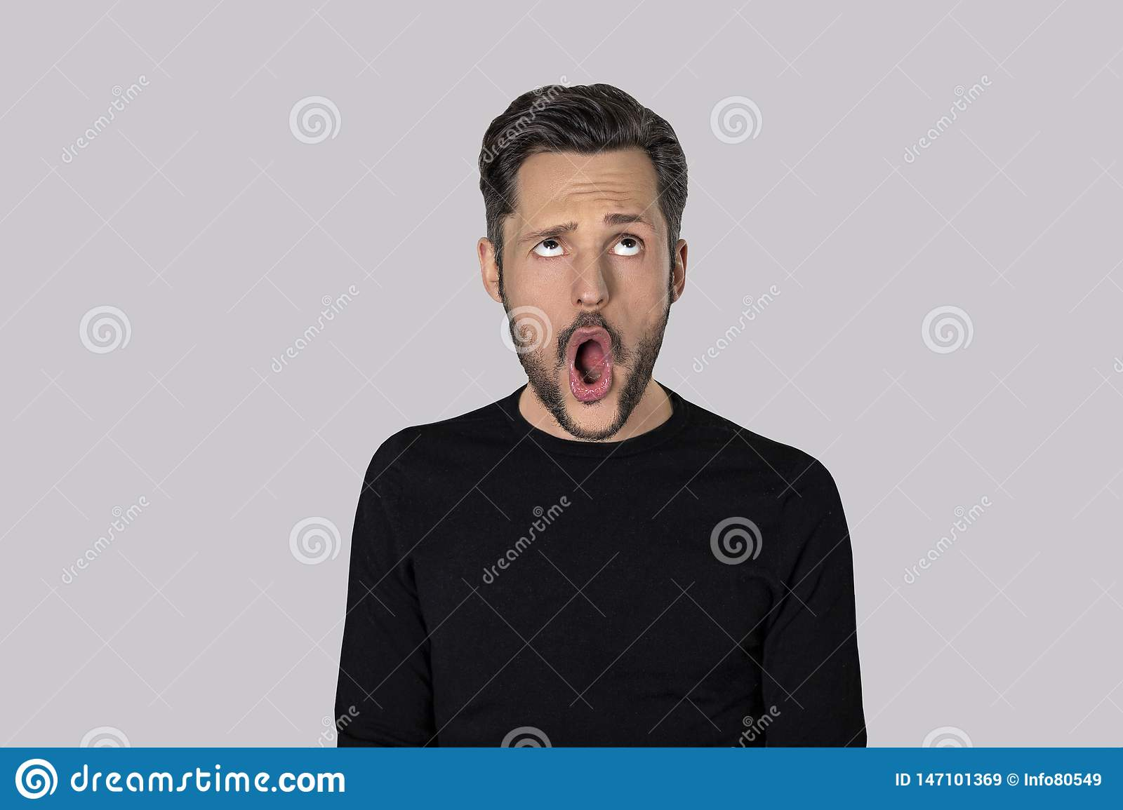 Portrait of young man with a funny expression isolated on grey background