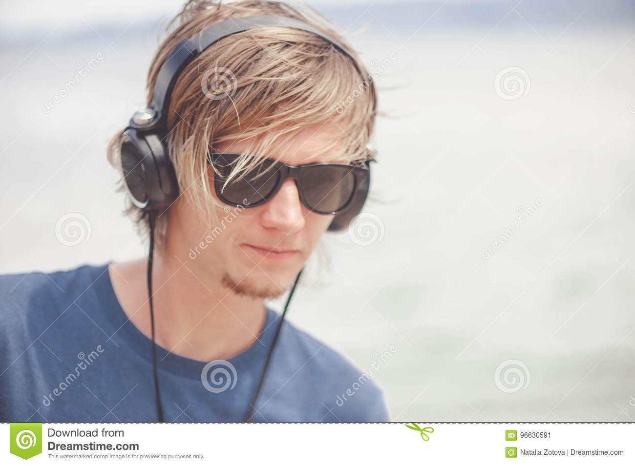 fff07bebe6c8 Handsome elegant man working with laptop and headphones watching a video  lecture on line at the beach