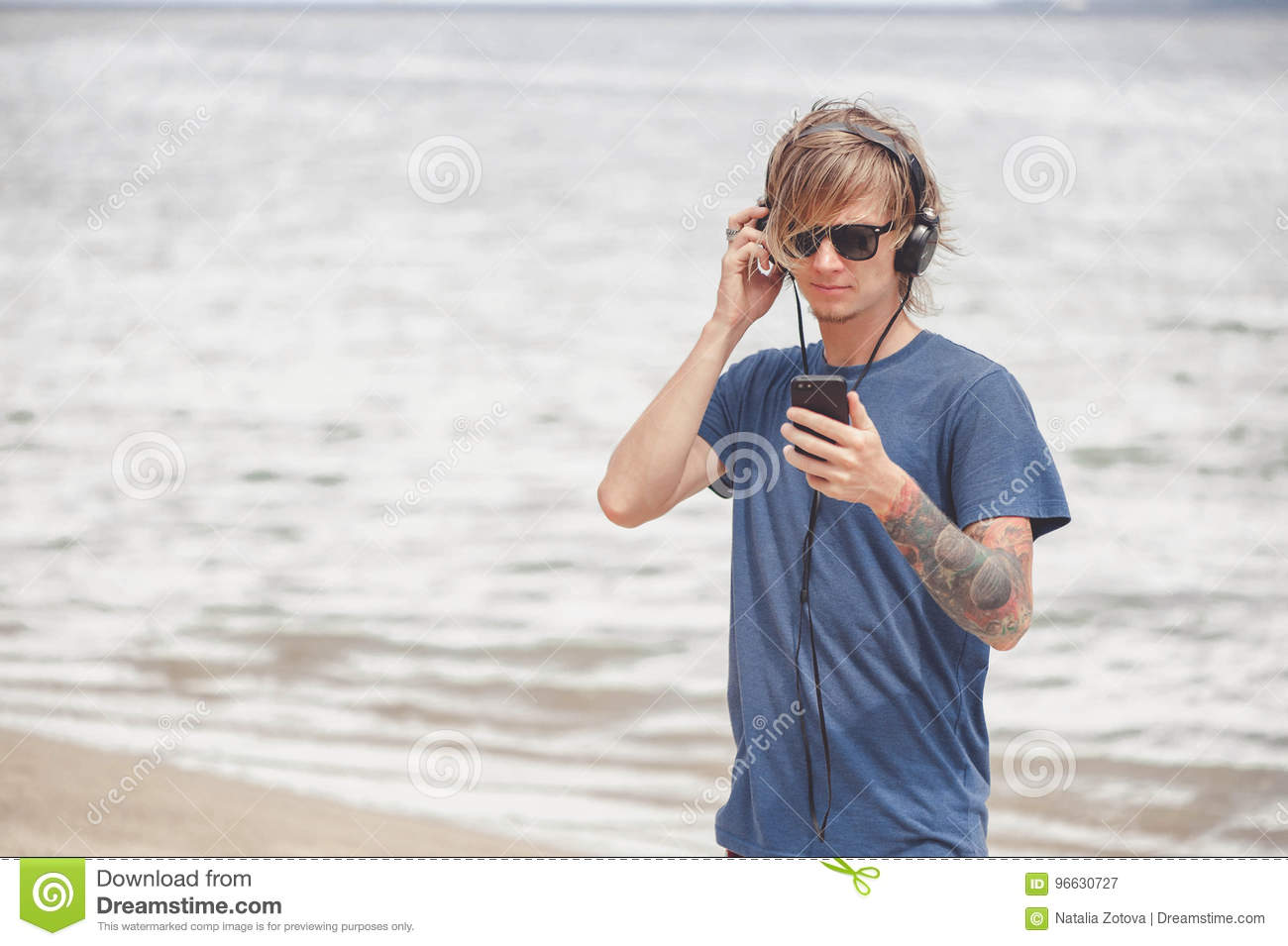 f18341fc8c34 Portrait Of Young Man In Headphones And Sunglasses At The Beach ...
