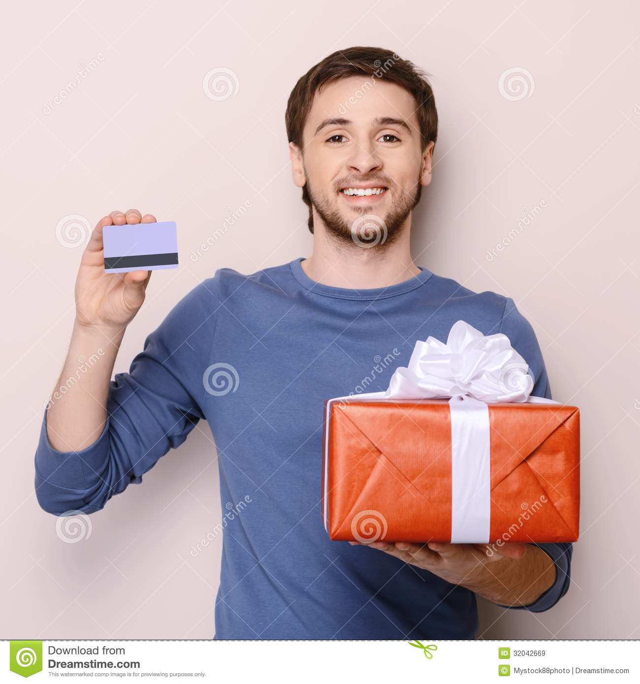 Portrait Of Young Man Holding Gift Box And A Credit Card