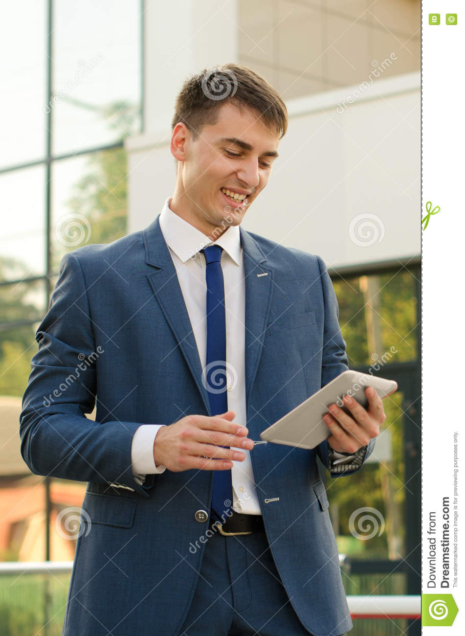 portrait of a young man professional banker working on touch pad while standing in modern office banker office space