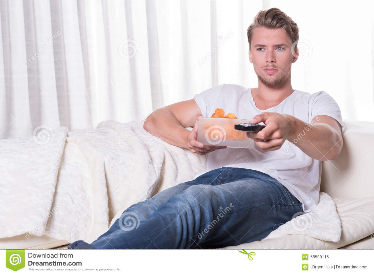 Portrait Young Man Sitting On Couch And Eating Chips And ...