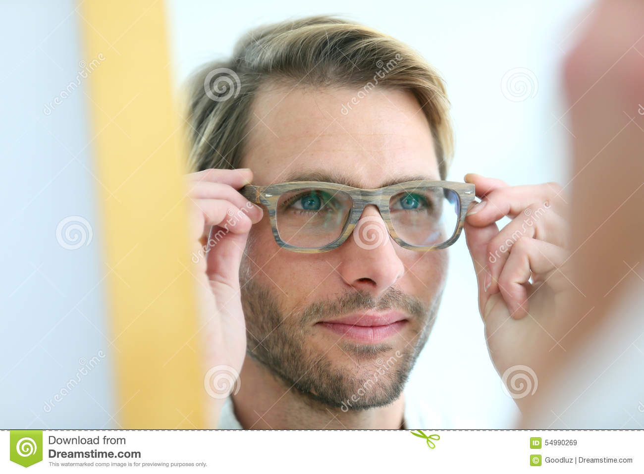 Portrait of young man trying on eyeglasses