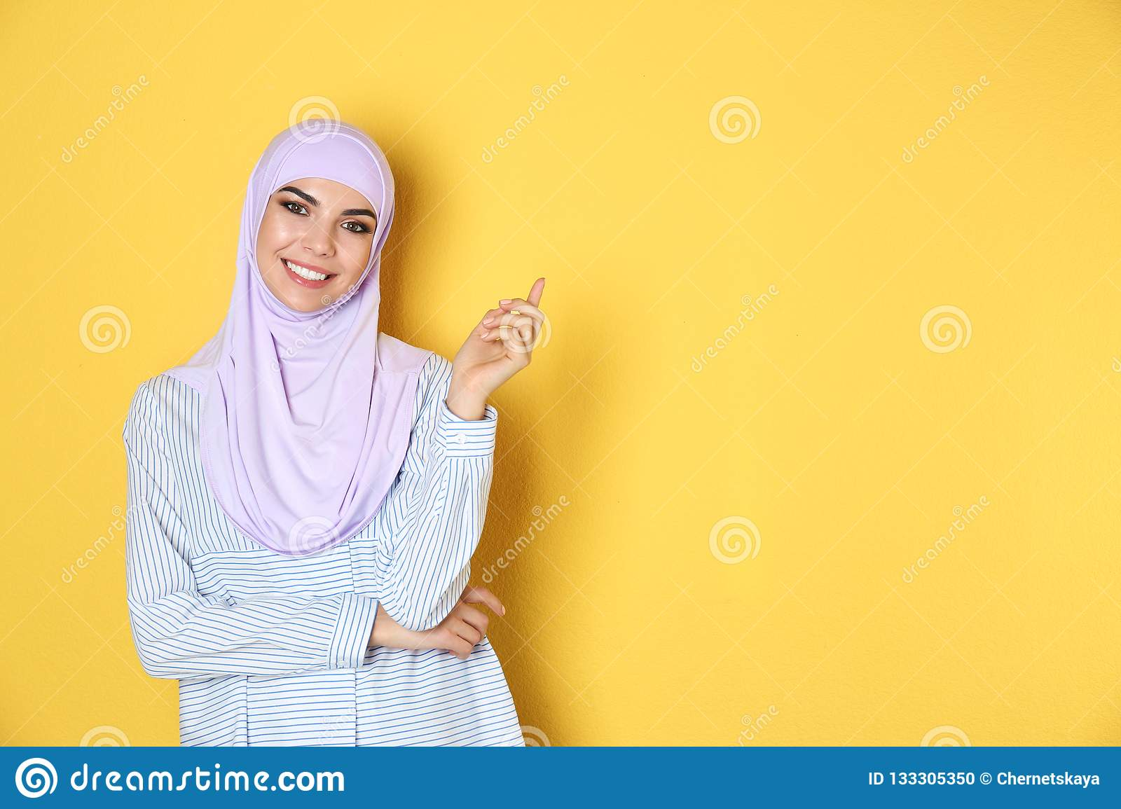 Portrait of young Muslim woman in hijab against color background.