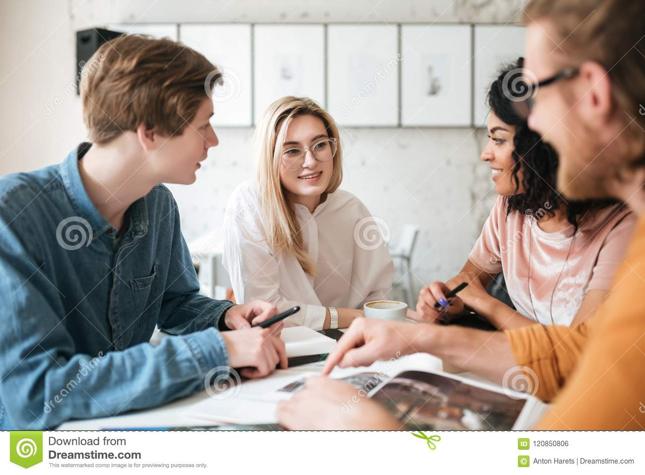 Young People Sitting In Office And Happily Looking At Each Other Discussion  Something. Group Of