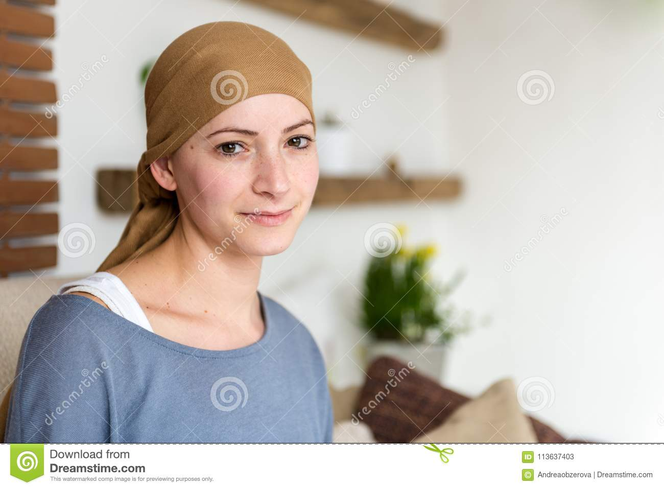 Portrait of young positive adult female cancer patient sitting in living room, smiling.