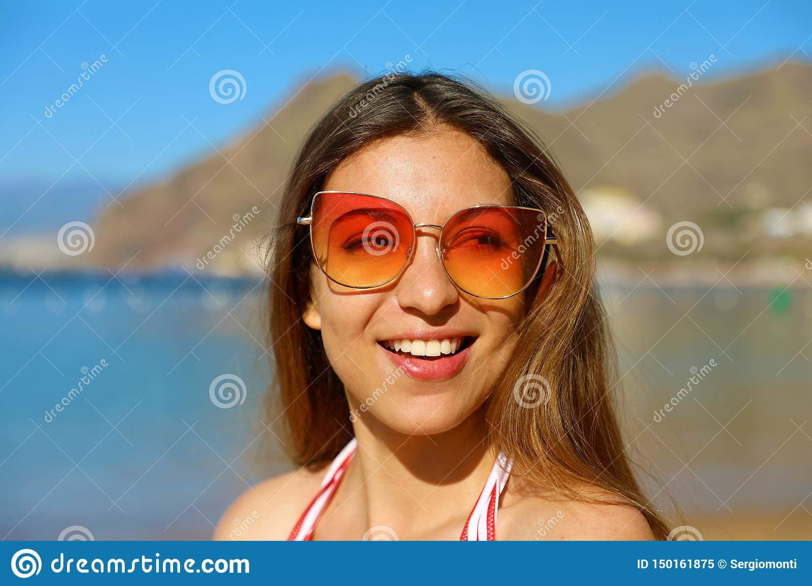 Portrait of young pretty woman with sunglasses on the beach