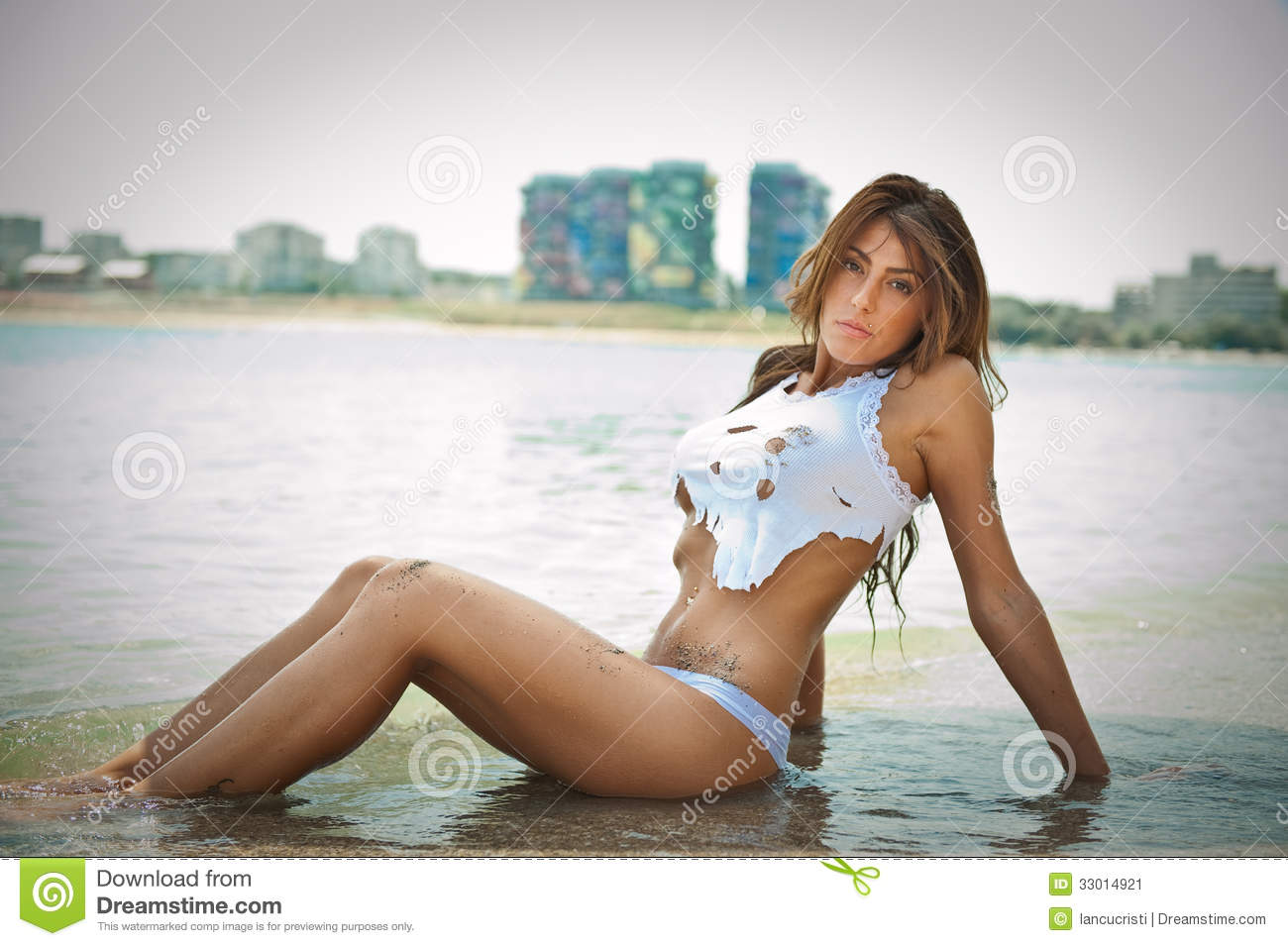 portrait of young brunette girl in white bikini and wet t-shirt at