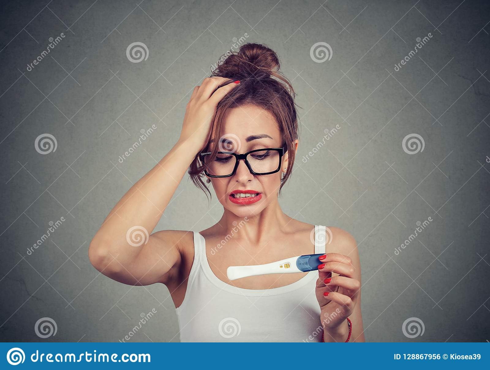 Portrait of a young shocked woman with pregnancy test