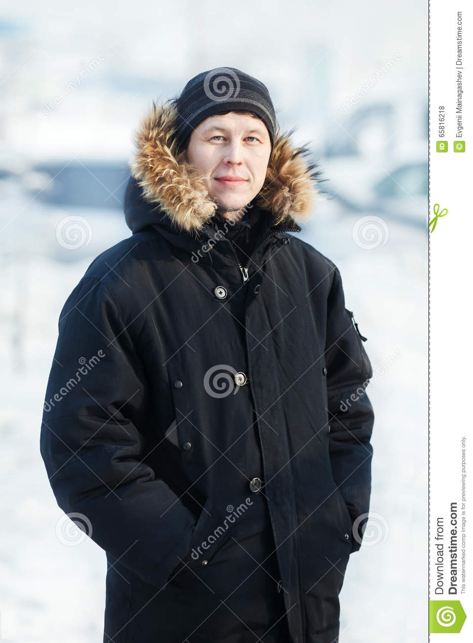 Portrait of a young Siberian man in cold winter day, wearing warm down jacket with fur hood, vertical. Snow, frost