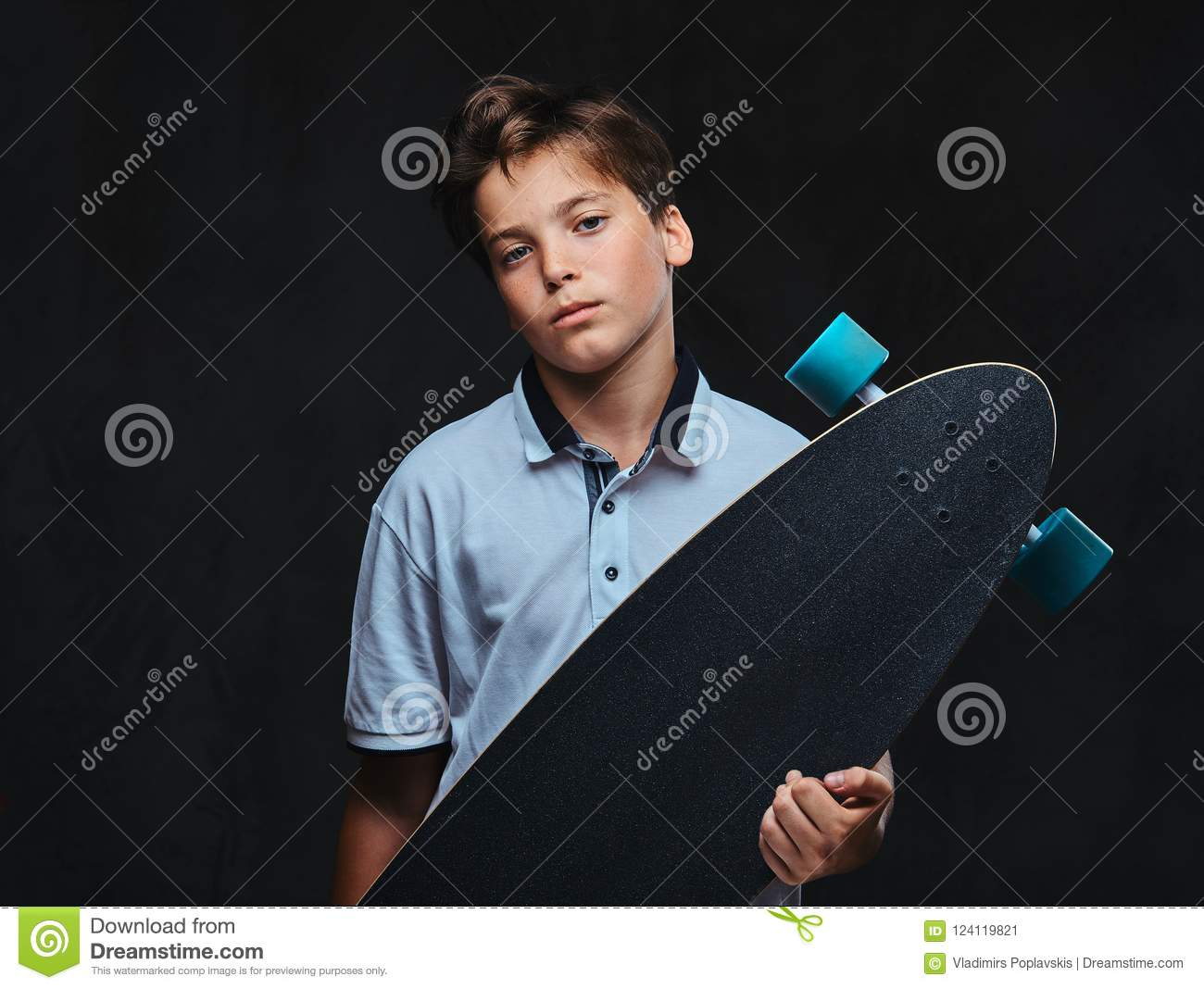 Portrait Of A Young Skater Boy Dressed In A White T Shirt Holds A