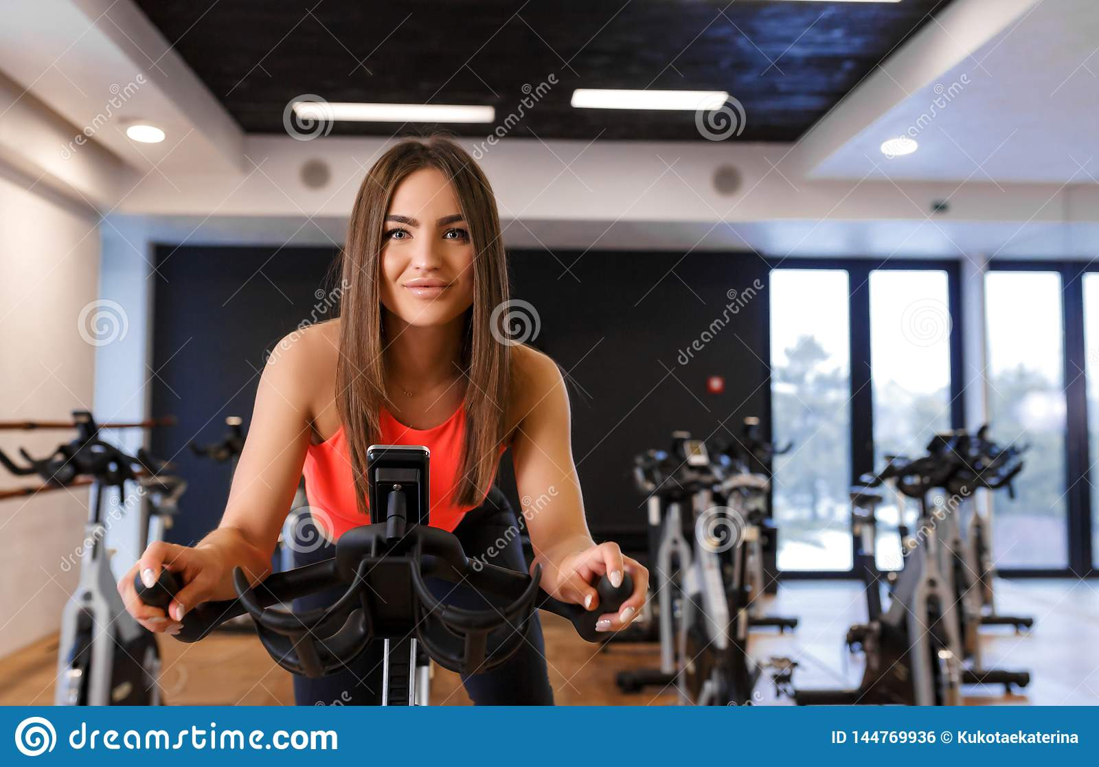 Portrait of young slim woman in sportwear workout on exercise bike in gym. Sport and wellness lifestyle concept