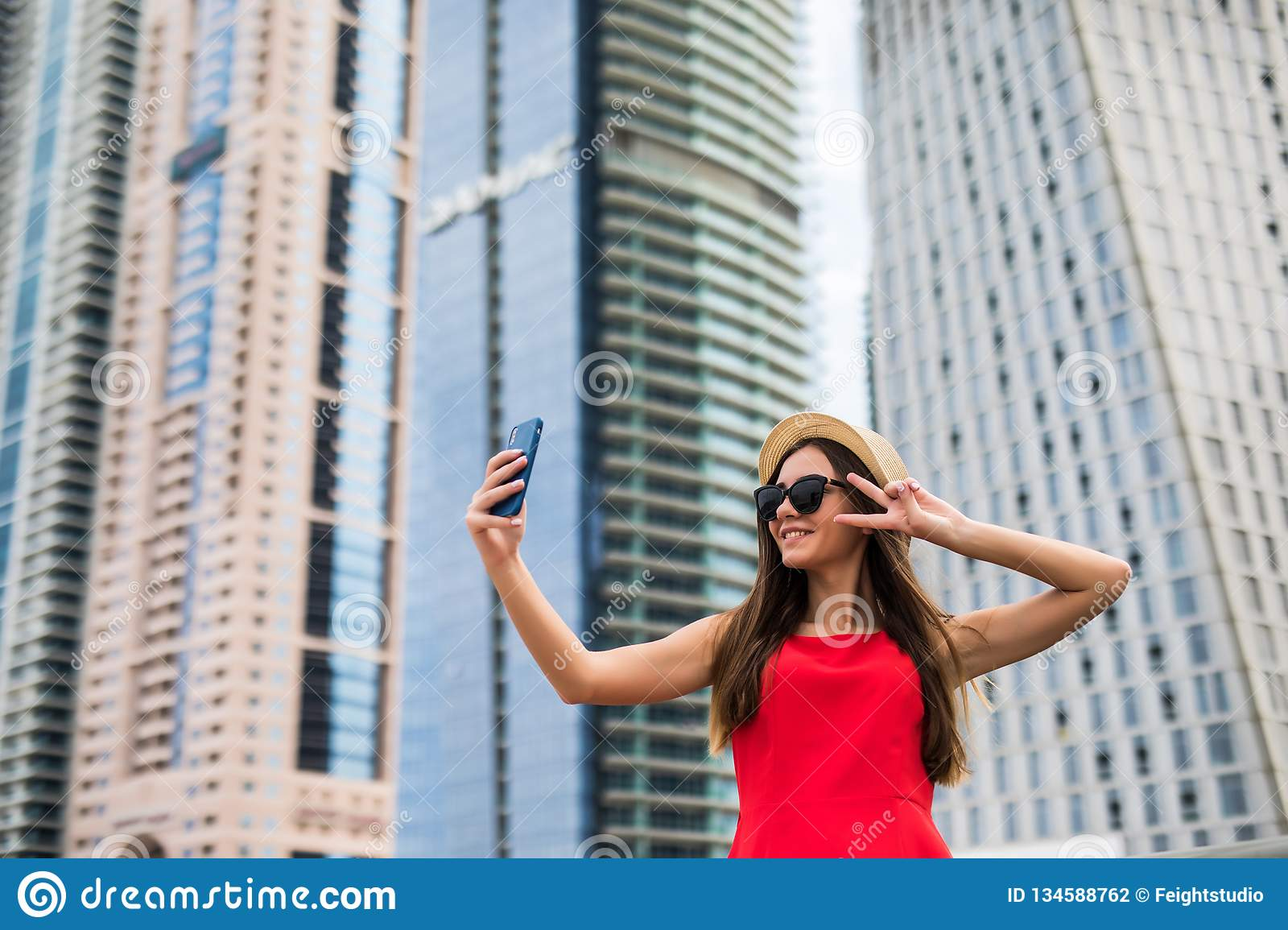Portrait of young smile woman in red dress, sunglasses and summer hat make video call with victory sign on the phone on downtown