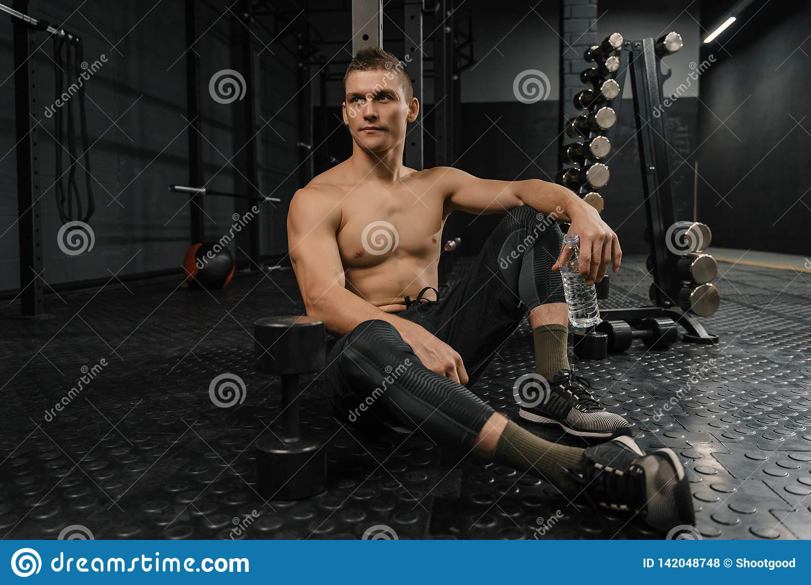 Portrait of young sporty man with bottle rest in gym after workout