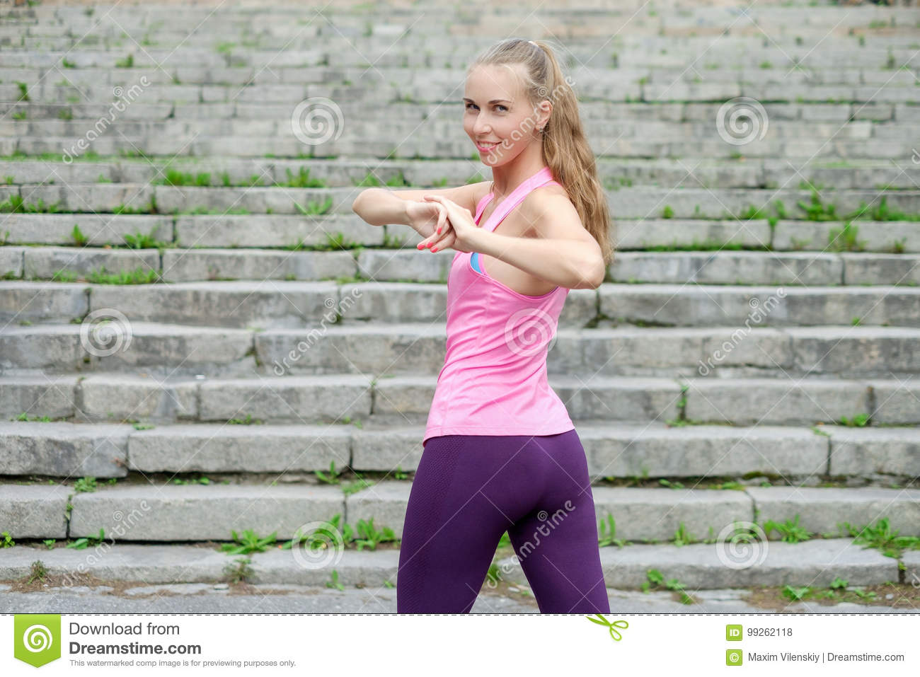 9833ffbe55ad Portrait of young sporty woman in sport dress does stretching exercises  outdoor