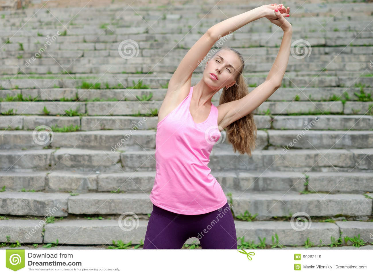 Portrait of young sporty woman in sport dress does stretching exercises outdoor