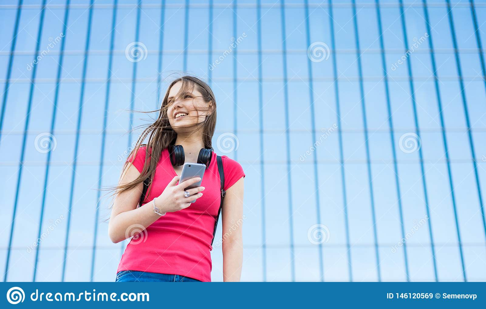 Portrait of young teenager brunette girl in coral t-shirt with long hair. girl on city looking on the smart phone. Glass building
