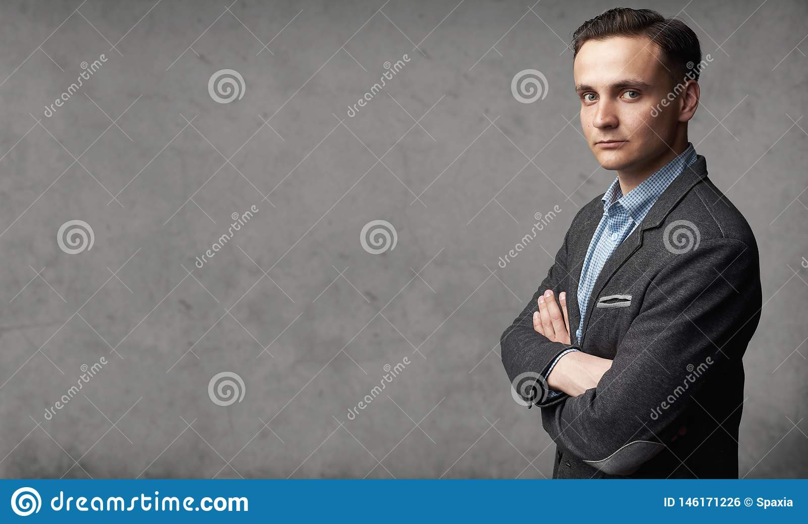 Portrait of young trendy man is standing before gray studio wall