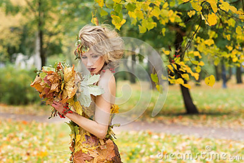Portrait of young woman. Autumn, dress with leafs. Park
