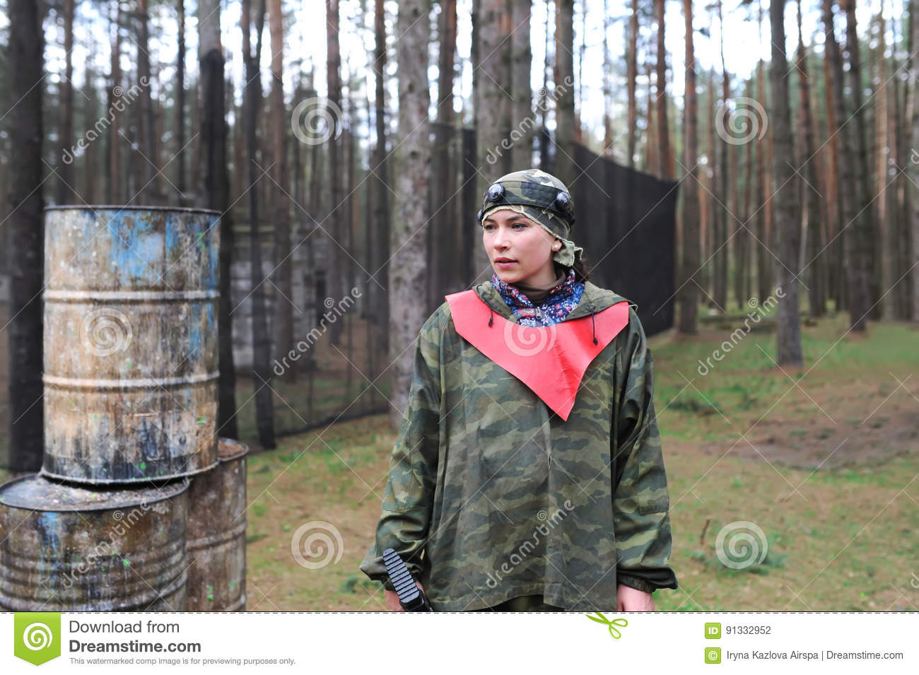 Portrait of young woman in camouflage with a rifle. Outdoors