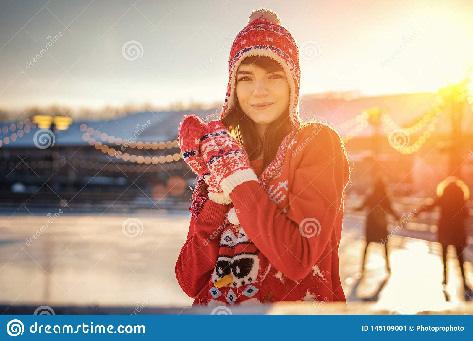 Portrait of a young woman in a hat on the ice rink, a smile on his face, the sun