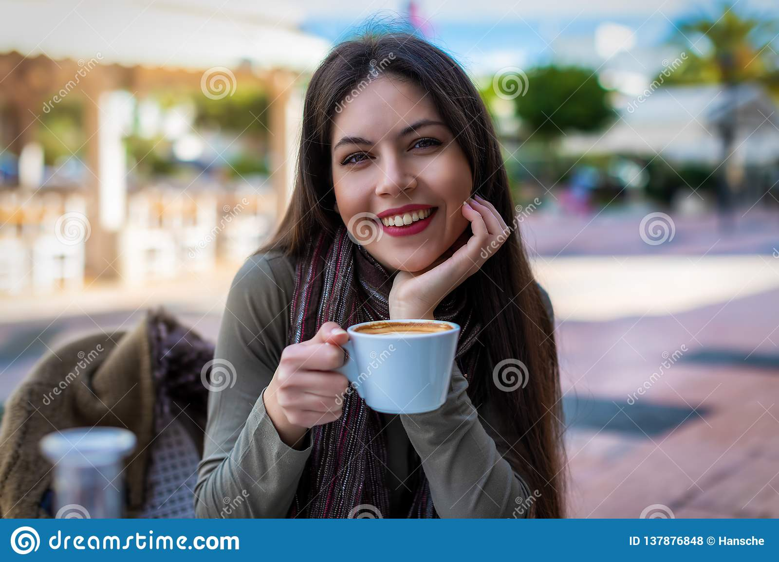 Portrait of a young woman holding a coffee cup