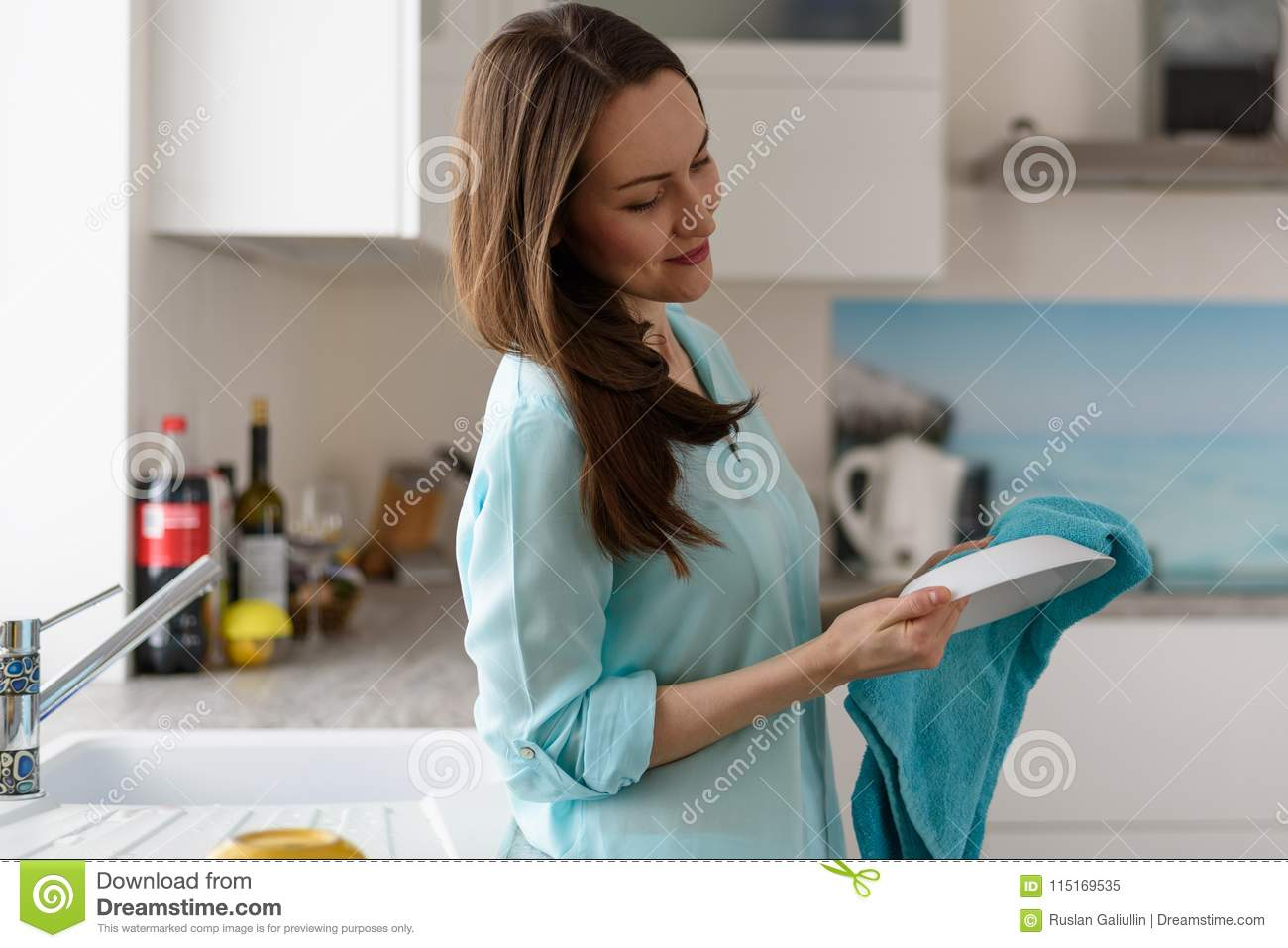 Portrait of a young woman in the kitchen interior wipe with a dry towel clean dishes, cleaning the house