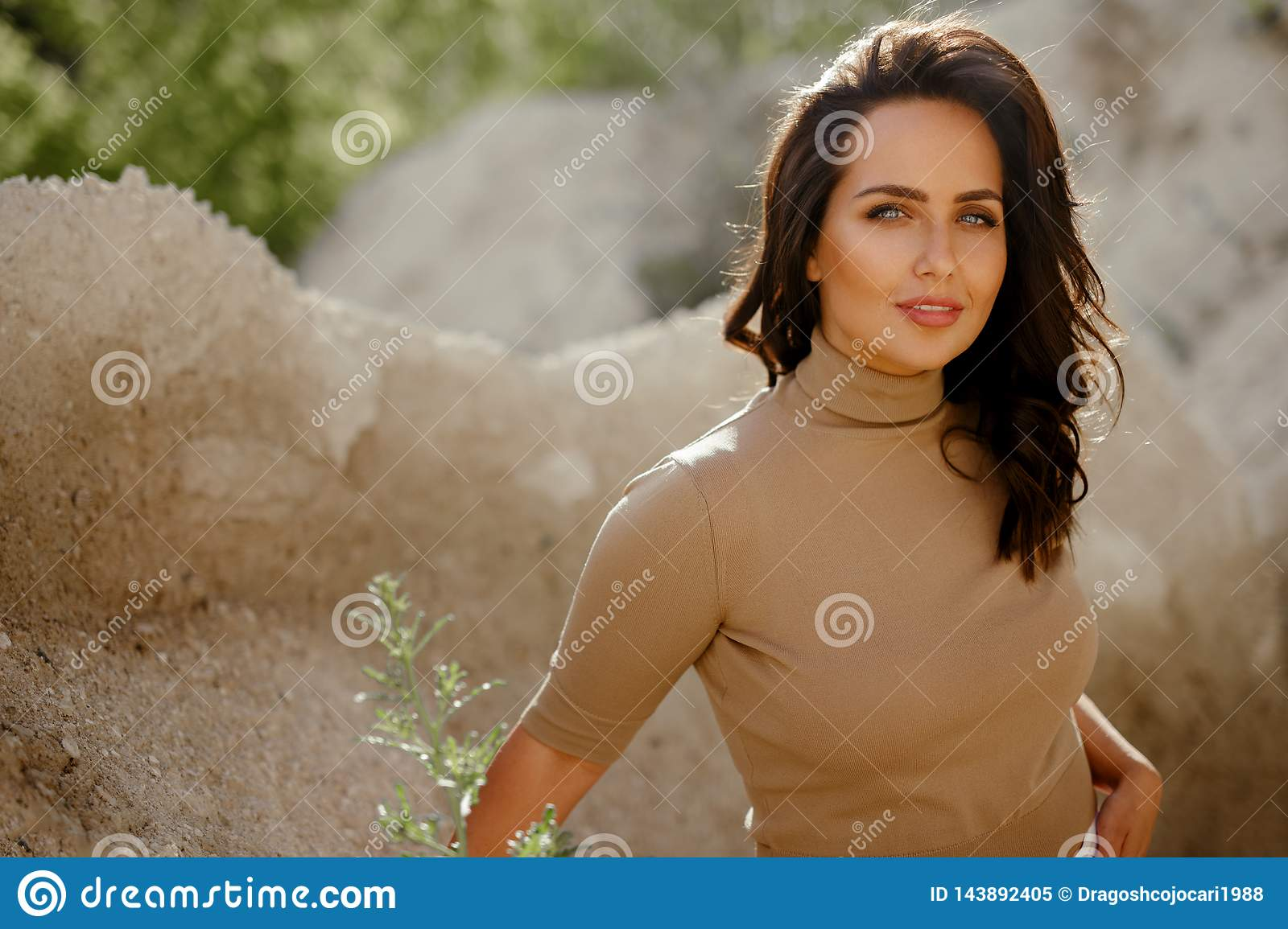 Portrait of gorgeous young woman looking at camera standing in nature, with copy space. Beauty concept
