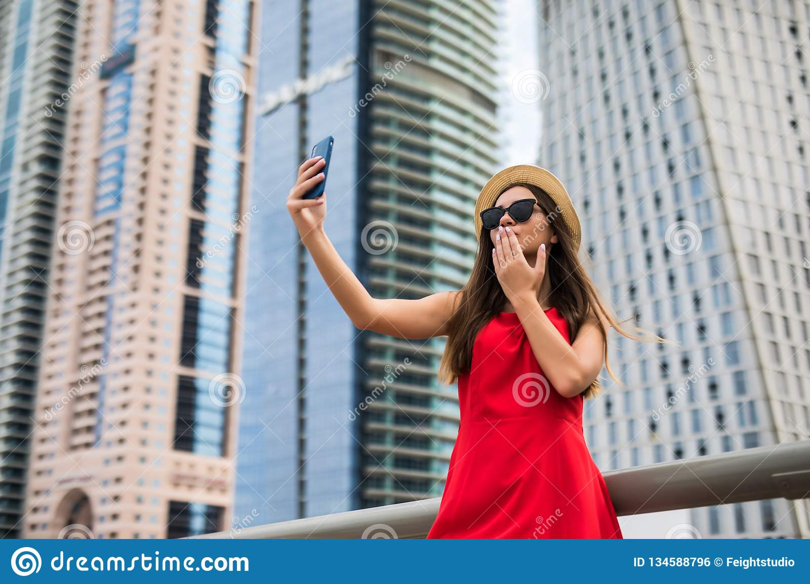 Portrait of young smile woman in red dress, sunglasses and summer hat make selfie or video call blow kiss on the phone on downtown