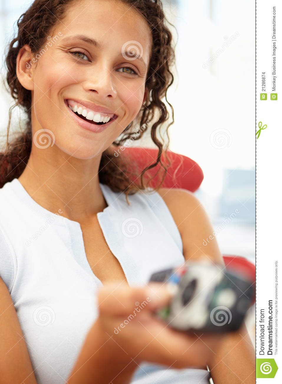 Portrait of young woman with remote control
