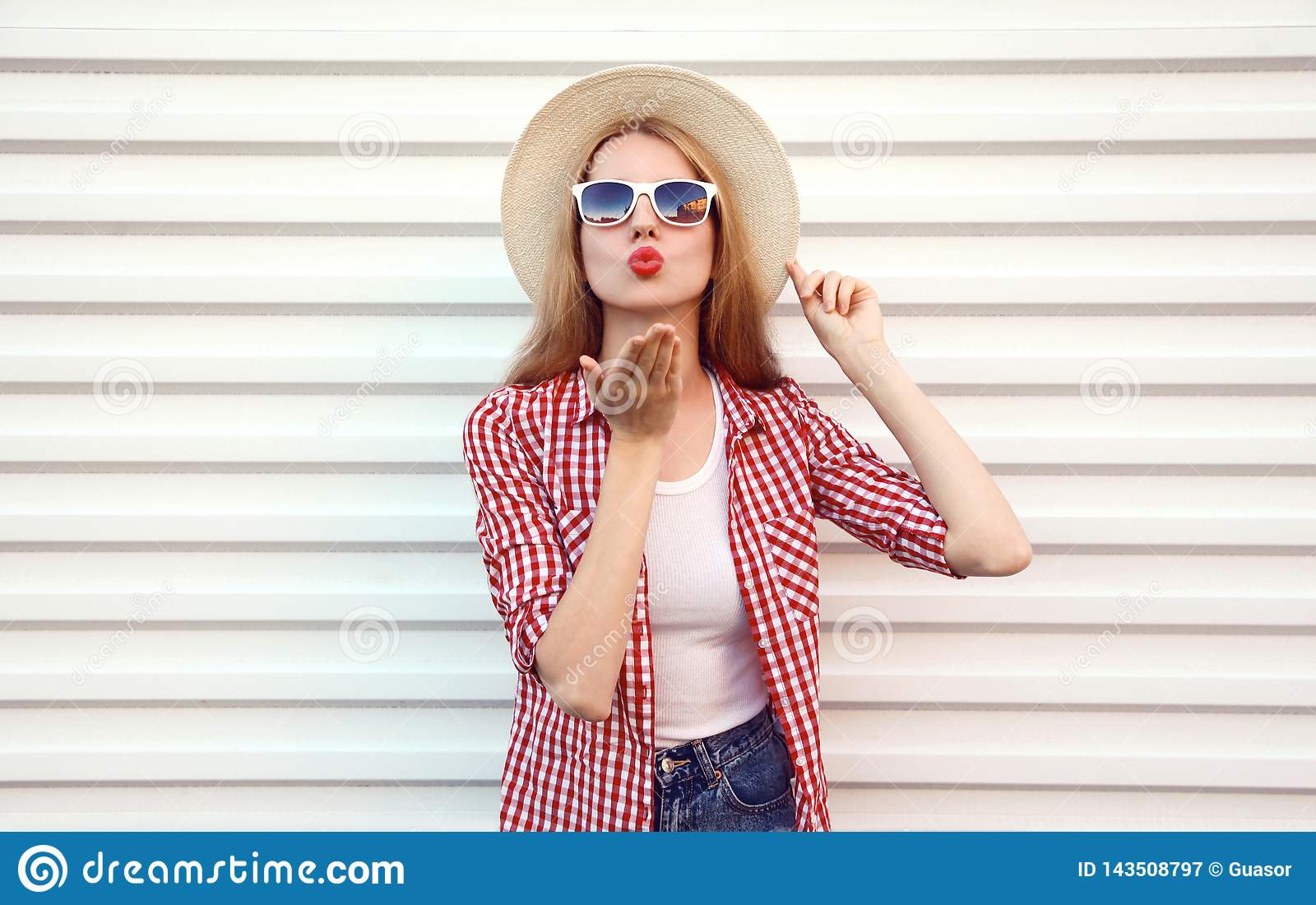 Portrait young woman sending sweet air kiss blowing red lips in summer round straw hat, checkered shirt on white wall