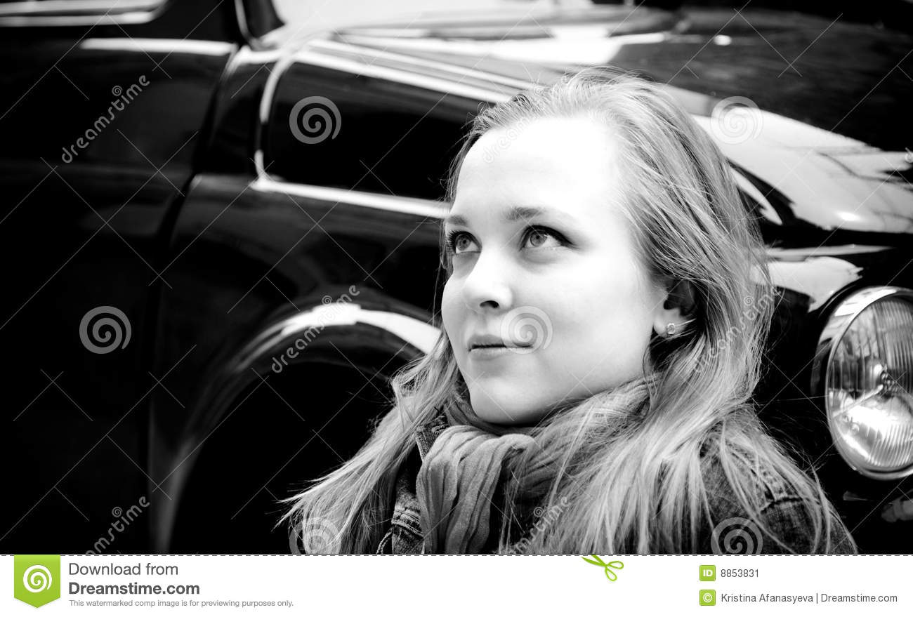 Portrait Of Young Woman Sitting Against Retro Car